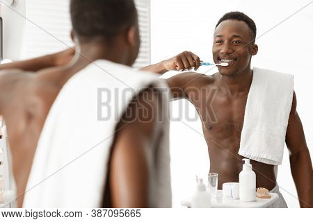 African American Man Brushing Cleaning Teeth Standing Near Mirror In Bathroom At Home. Toothcare Mor