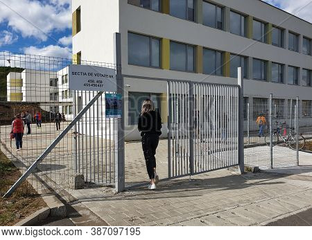 Floresti, Romania - September 27, 2020: Local Elections Day In Romania. Girl Entering To Vote On Loc