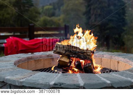 Outdoor Fireplace With A Bright Yellow Flame In A Fire Pit And Autumn Forest Background. Rest And Re
