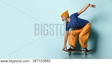 Gray-bearded Grandfather In A T-shirt, Orange Pants And A Hat, Sneakers, Bracelets. Crouching While