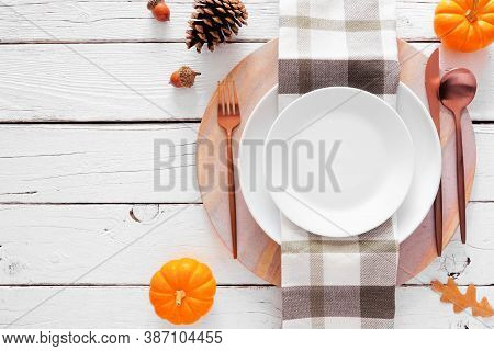 Autumn Harvest Or Thanksgiving Dinner Table Setting With Plate, Flatware, Check Print Napkin, Pumpki