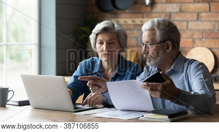 Senior Couple Pay Bills Online On Laptop