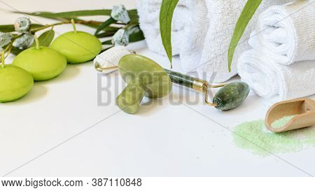 Spa Chinese Face Care Tools. Jade Gem, Jade Roller, Eucalyptus Salt And Candles On The White Backgro