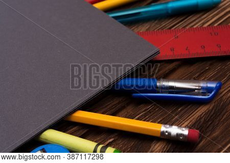 Many Different Stationery On A Wooden Surface Under A Dark Gray Sheet Of Paper. Flat Lay. Gray Empty