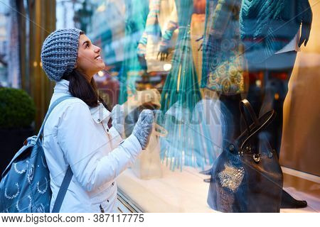 Young woman standing front of shop window with desire at wintertime.