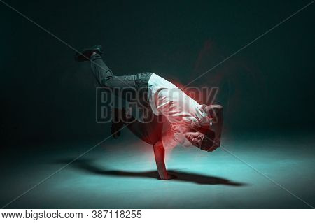 Stylish Young Guy Breakdancer Dancing Hip-hop In Neon Light. Long Exposure Shot. Battle Competition