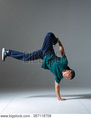 Cool Guy Breakdancer Dance On The Floor Standing On One Hand Isolated On Gray Background. Breakdance