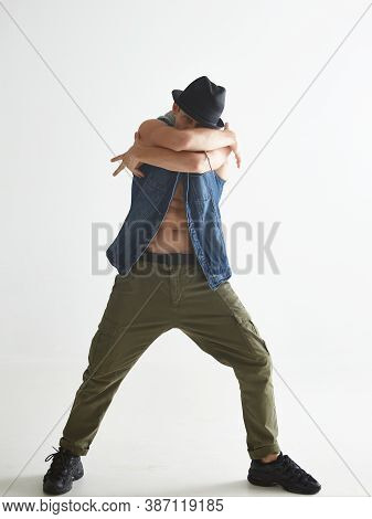 Stylish Guy Dancer In Hat Dancing Contemporary Dance In Studio Isolated On White Background. Breakda