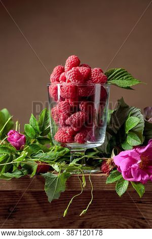 Fresh Juicy Raspberries In Glass Bowl. Summer Still Life With Raspberries, Meadow Grasses And Flower