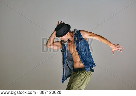 Young Guy Breakdancer In Hat Dancing Expressive Dance In Studio Isolated On Gray Background. Dance S