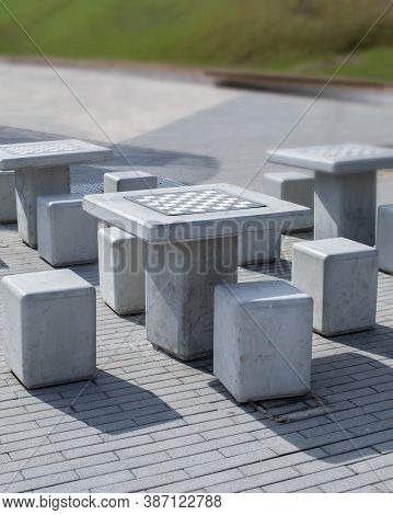 Chess Table Checkerboard In The Park. Chessboard Table And Chairs In Gray Concrete, Modern Minimalis