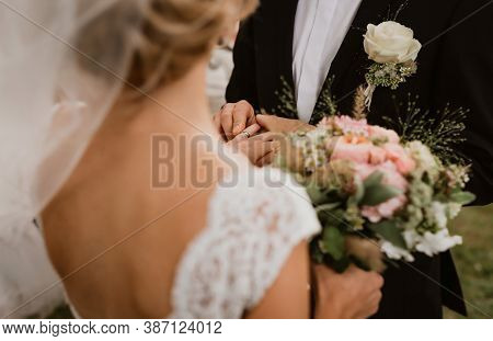 The Groom Is Putting The Wedding Ring On The Bride. Image Has Been Taken Over The Shoulder Of A Brid