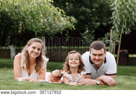 Father, Mother And Two Children, Baby Girl And Little Daughter On The Grass On Summer Day. Happy Fam