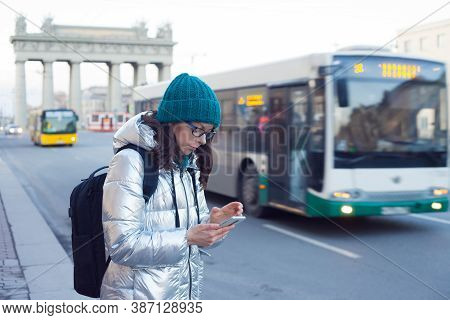 Woman In A Down Jacket And Hat Stands At A Public Transport Stop And Uses A Smartphone. Wait For The