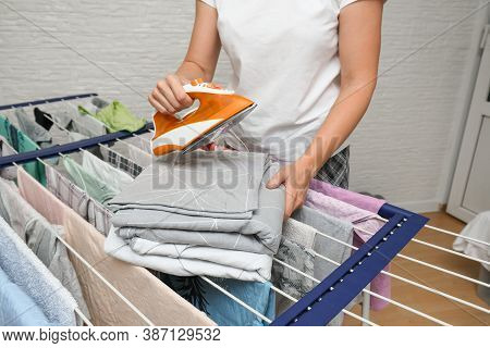 Unrecognizable Woman Collecting Dry Clean Clothes From A Drying Rack And Putting It In Stack For Iro
