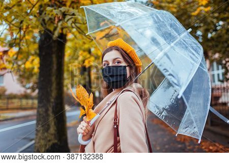 Stylish Young Woman In Protective Mask Walking Along Autumn City Street Under Transparent Umbrella D