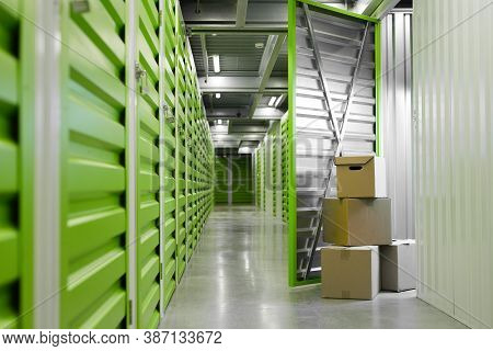 Background Image Of Green Self Storage Facility With Opened Unit Door And Cardboard Boxes, Copy Spac