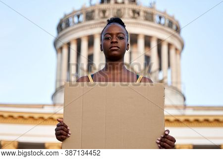 Young African Woman Activist Stand Outdoor Hold Empty Blank Sign Protesting On Street. Black Female