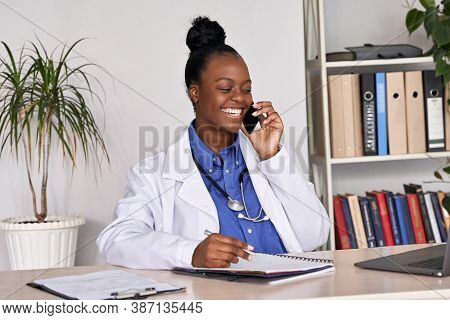 Smiling African American Female Doctor Physician Holding Cell Phone Talking On Mobile At Work. Healt