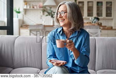 Happy Beautiful Relaxed Mature Older Adult Grey-haired Woman Drinking Coffee Relaxing On Sofa At Hom