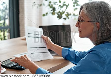 Senior Mature Business Woman Holding Paper Bill Using Calculator, Old Lady Managing Account Finances