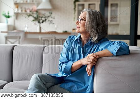 Calm Relaxed Mature Older Woman Relaxing Sitting On Couch At Home. Peaceful Middle Aged Grey-haired