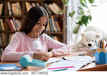 Happy Smiling Indian Latin Preteen School Girl Pupil Studying At Home Sitting At Desk. Smart Cute Hi