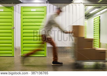 Blurred Motion Shot Of Unrecognizable Man Pushing Cart With Boxes While Running In Self Storage Faci