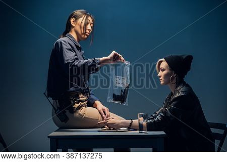 An Experienced Investigator During An Interrogation At A Police Station Shows The Criminal Girl The