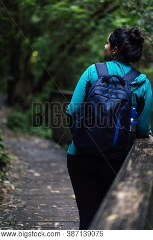 Woman Standing On The Side Of A Bridge In The Middle Of The Woods. Ecotourism Concept. Vertical Phot