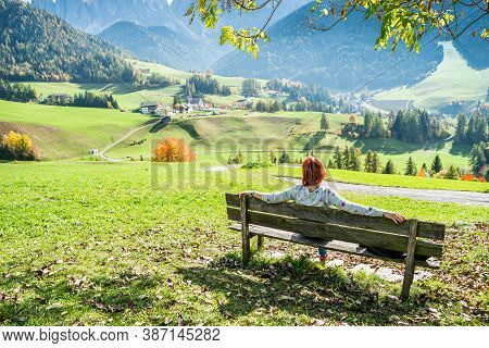 Woman Sitting On Bench And Enjoying The View Village Of Santa Magdalena On The Slopes Of The Dolomit