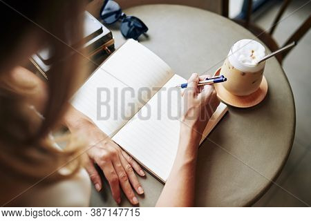 Creative Young Woman Drinking Coffee At Cafe Table And Writing In Journal Her Thoughts And Ideas
