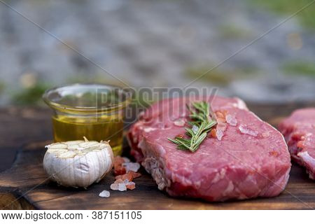 Raw Meat Beef Steak Organic Fresh Ingredient On Wooden Board Table Background In Kitchen With Rosema