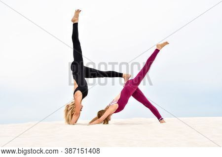 Two Beautiful Young Women Performing Yoga Pose Eka Pada Adho Mukha Svanasana On The Beach,steamy Yog