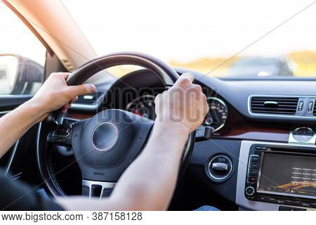 A Man Holds The Steering Wheel Of A Car With Two Hands, A View From The Salon. Car Driving.