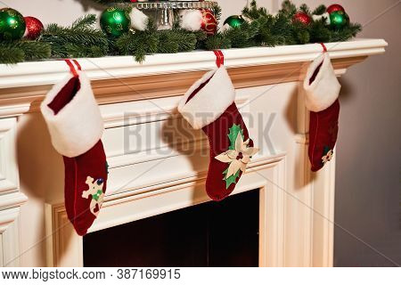 Christmas Socks Hanging On Fireplace In Room Interior. Christmas Socks With Gifts On The Fireplace.