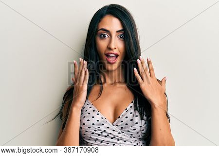 Beautiful hispanic woman wearing casual clothes scared and amazed with open mouth for surprise, disbelief face