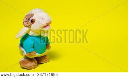 Toy Plush Soft Lamb Ram Sheep In Clothes On A Yellow Background. Baa-lamb. Banner For Toy Shop With
