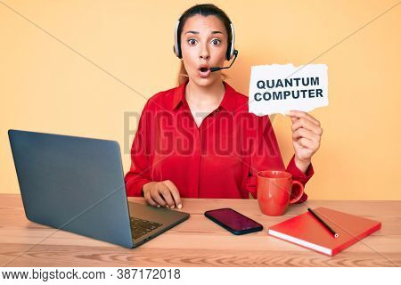 Young brunette woman holding quantum computer banner scared and amazed with open mouth for surprise, disbelief face