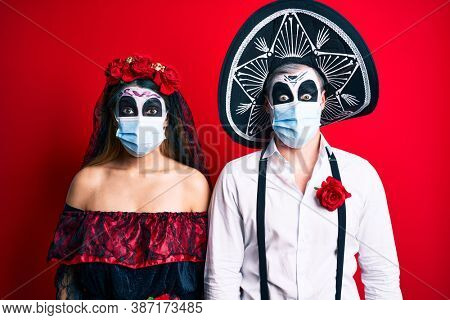 Couple wearing day of the dead costume wearing medical mask scared and amazed with open mouth for surprise, disbelief face