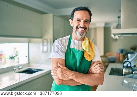 Middle age housekeeping man with beard smiling happy standing at the kitchen