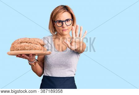 Young blonde woman holding wholemeal bread with open hand doing stop sign with serious and confident expression, defense gesture