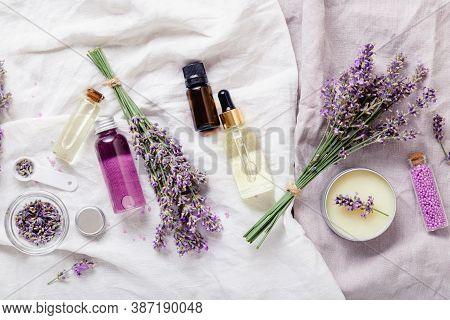 Lavender Oils, Serum Liquids Butter Parfumes, Lavender Flowers On White Fabric. Set Skincare Spa Bea