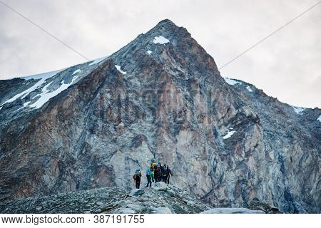 Zinal, Switzerland - July 19, 2019: Back View Of Hikers Team With Backpacks Walking On Rocky Path An