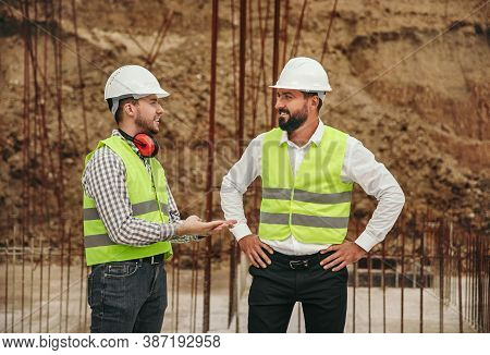 Cheerful Male In Waistcoats And Helmets Smiling And Talking With Each Other While Working On Constru