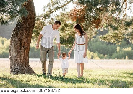 Happy Family Walking In The Park Holding Hands And Smiling. Mom, Dad And Son Spending Time Together