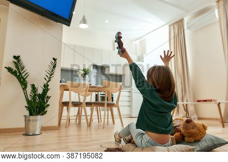 A Small Girl Sitting On A Floor In Front Of A Tv Cheering After Winning A Videogame Holding A Gamepa