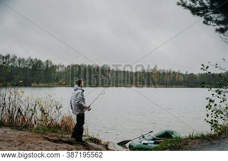 Fisherman With A Fishing Rod Near An Inflatable Boat, With Boxes With Fishing Tackles, Is Standing O