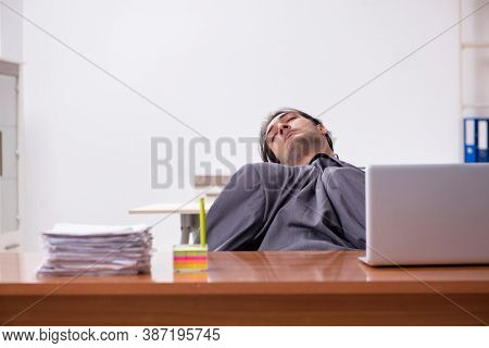 Young male employee sleeping in the office