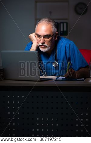 Aged male doctor in the hospital at night